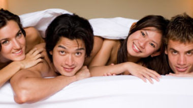 Swingers laying naked in a bed